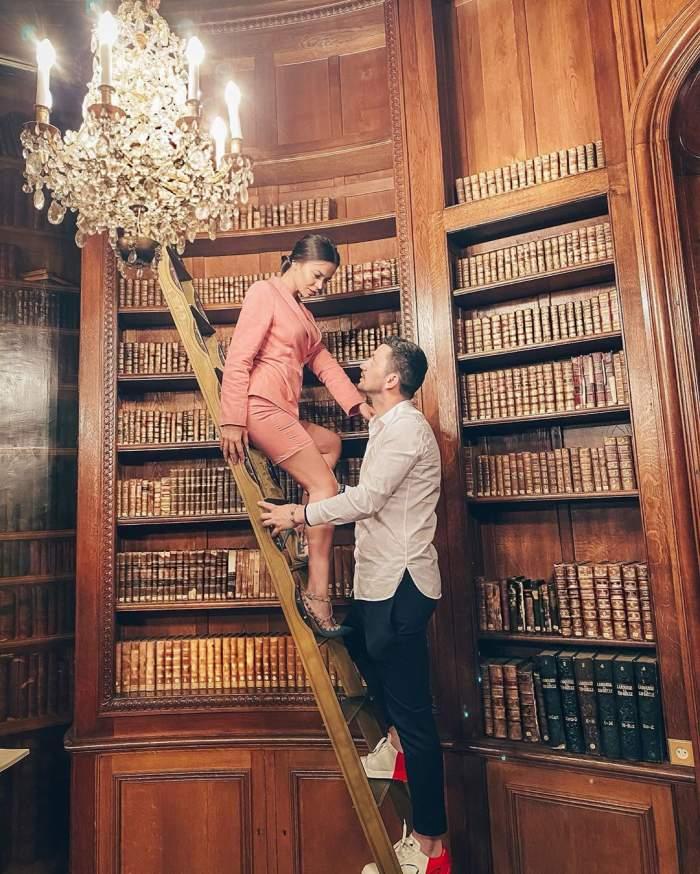 Denisa Hodișan și Flick, fotografiați într-o bibliotecă, privindu-se cu multă dragoste