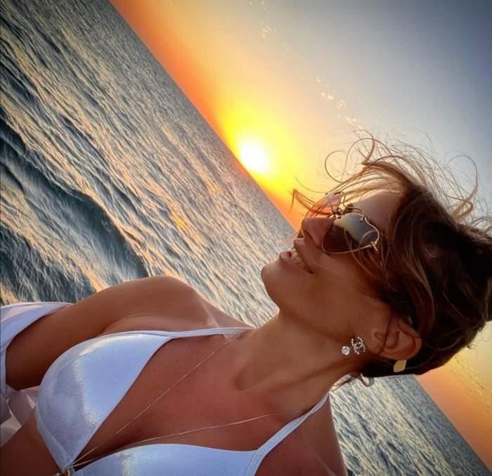 Crina Abrudan, în sutien alb, pe plajă, câmbitoare, cu soarele pe fundal