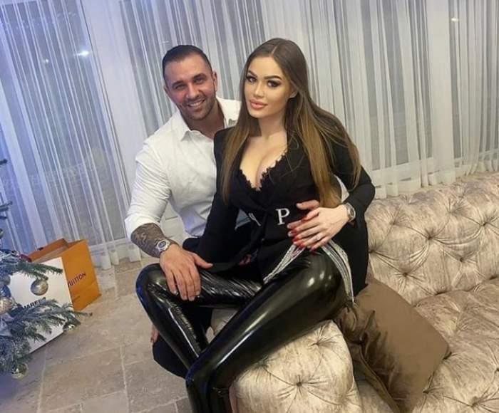 Daria Radionova și Alex Bodi, îmbrățișați pe canapea, ea în negru, el în alb