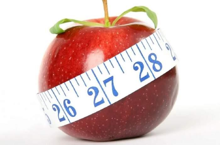 Un măr roșu ce este înconjurat de un metru.
