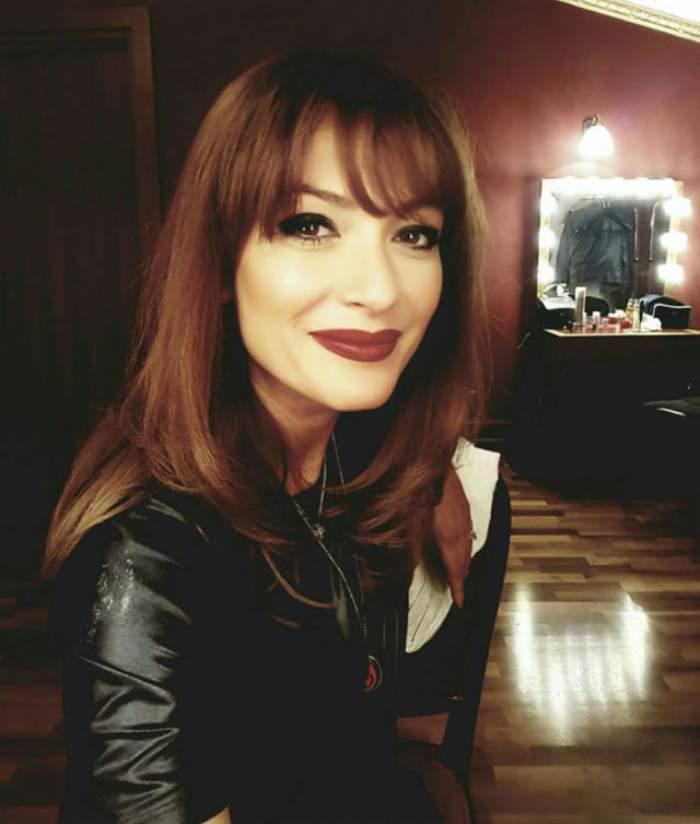 Anca Țurcașiu, îmbrăcată în negru, cu ruj roșu, zâmbitoare, în casă