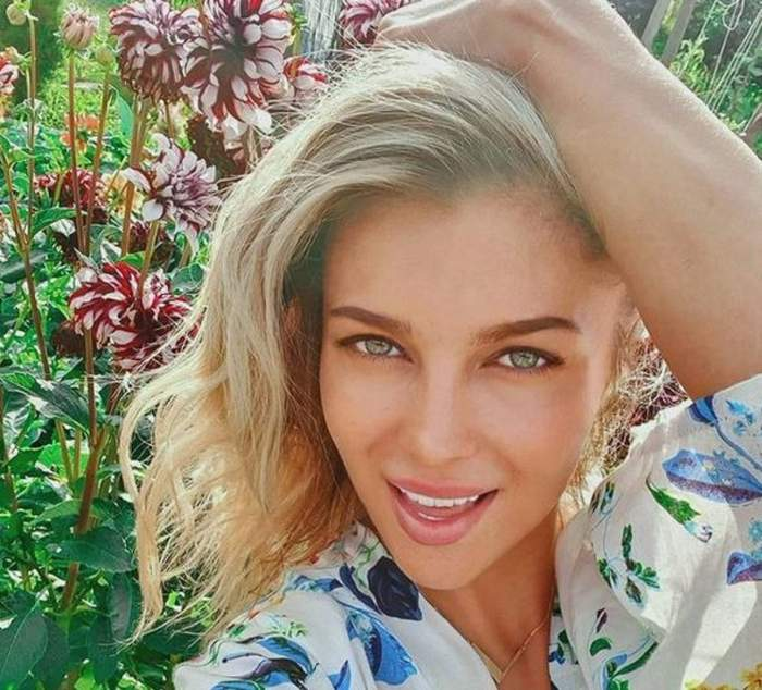 Lora poartă o rochie albă cu detalii albastre. Vedeta își ține o mână prin păr și în spatele ei se pot vedea niște flori roșii.