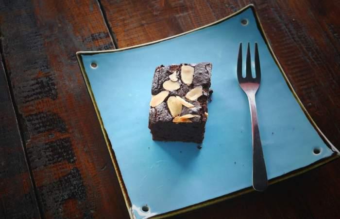 O bucată de prăjitură negresă așezată pe o farfurie albastră. Lângă ea este o furculiță.