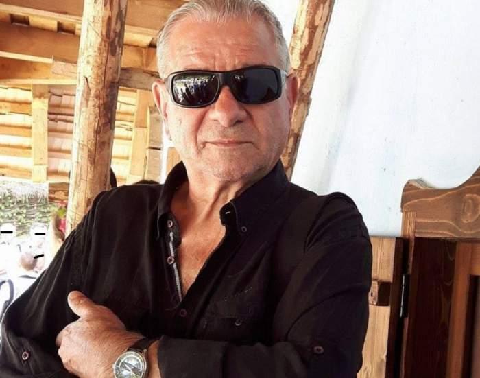 Viorel Nimigeanu purta o cămașă neagră și ochelari de soare. Artistul avea la mână un ceas și ține mâinile în sân.