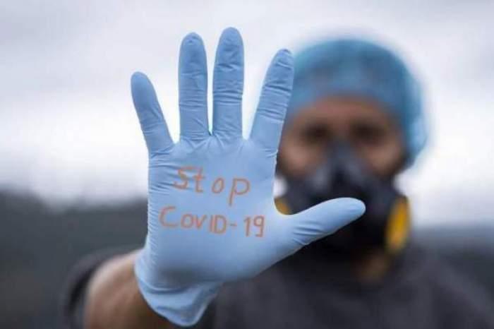 """Mâna unui medic, cu mănușă, pe care scrie """"stop COVID-19"""""""