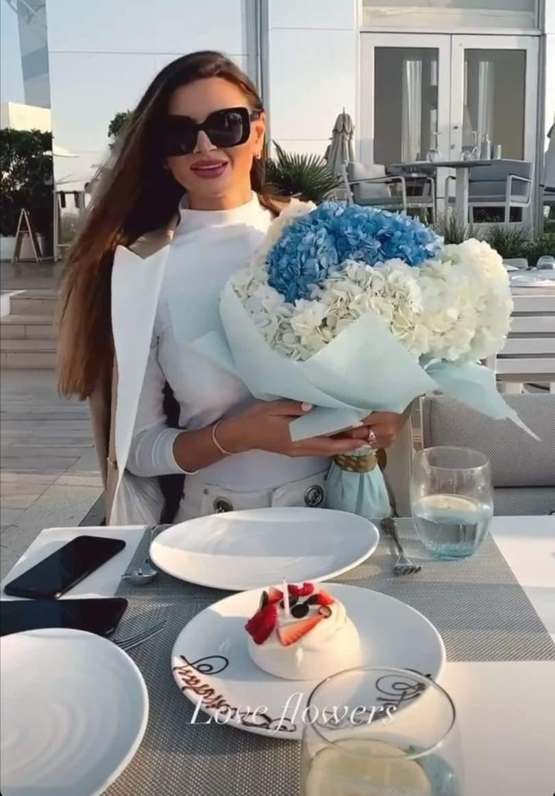Ramona Gabor, îmbrăcată în alb, ținând în brațe un buchet de flori albe și albastre