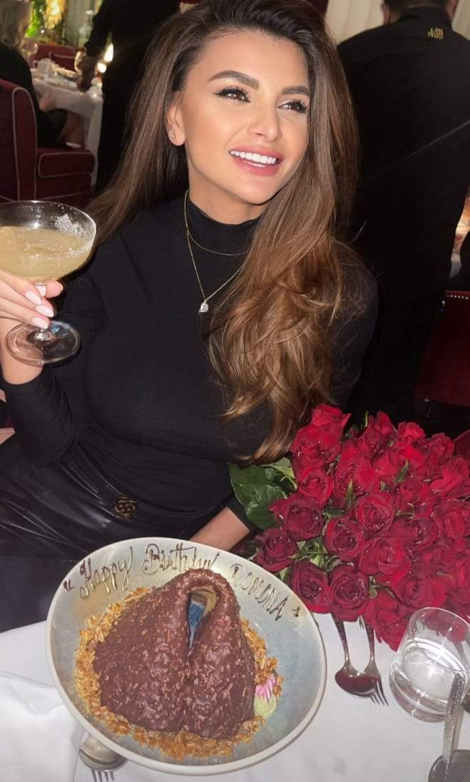 Ramona Gabor, la masă,  cu paharul în mână, cu tort în față și un buchet de trandafiri roșii alături