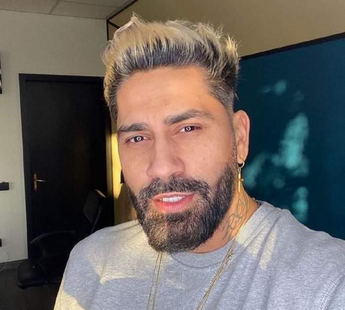 Connect-R poartă un tricou gri. Artistul își face un selfie și are la gât un lanț auriu.