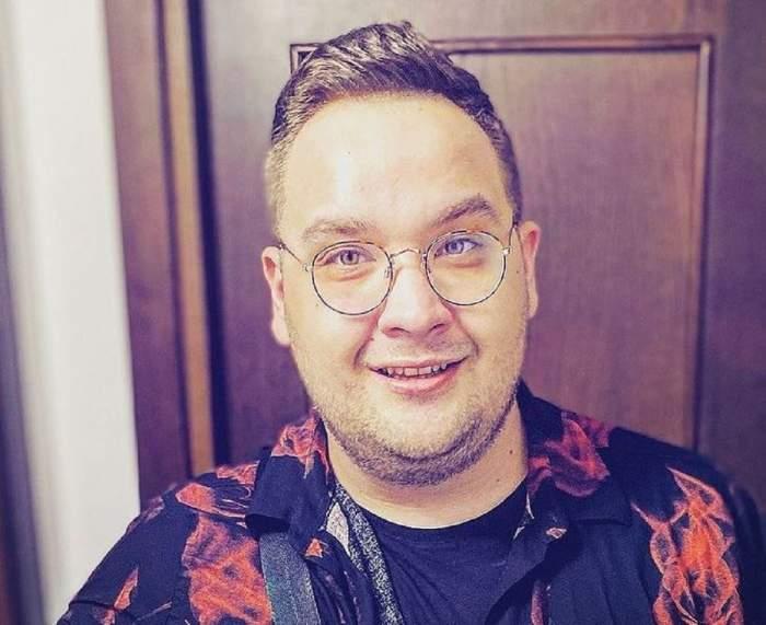 Răzvan Babană cu ochelari de vedere. Fostul concurent de la Chefi la cuțite poartă o cămașă neagră cu imprimeu roșu.