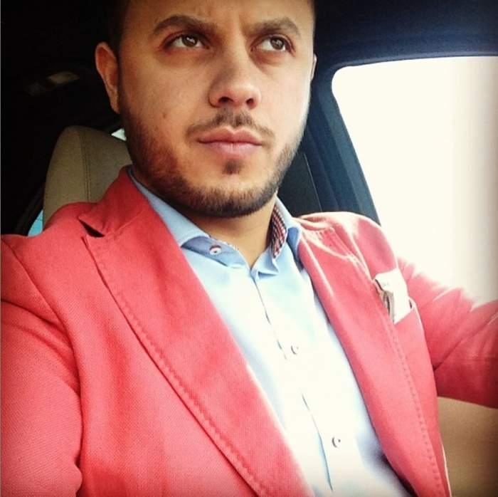 Gabi Badalau este in masina, poarta un sacou roz cu camasa alba
