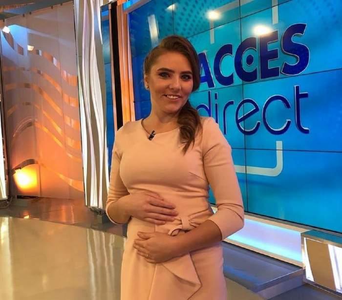 Veronica este în platoul Acces Direct. Tânăra poartă o rochie crem și zâmbește larg, având mâinile pe burtă.