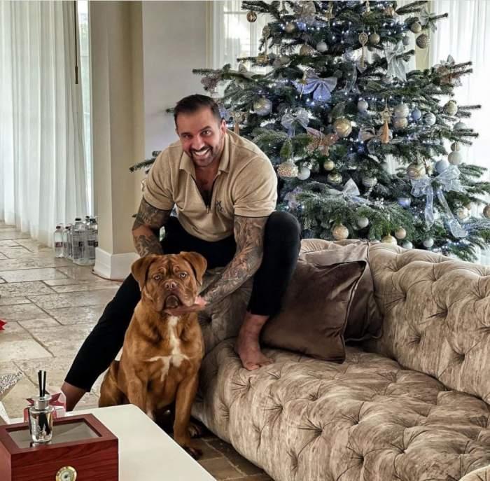 Alex Bodi este in living, sta pe marginea canapelei, se joaca cu cainele lui si zambeste