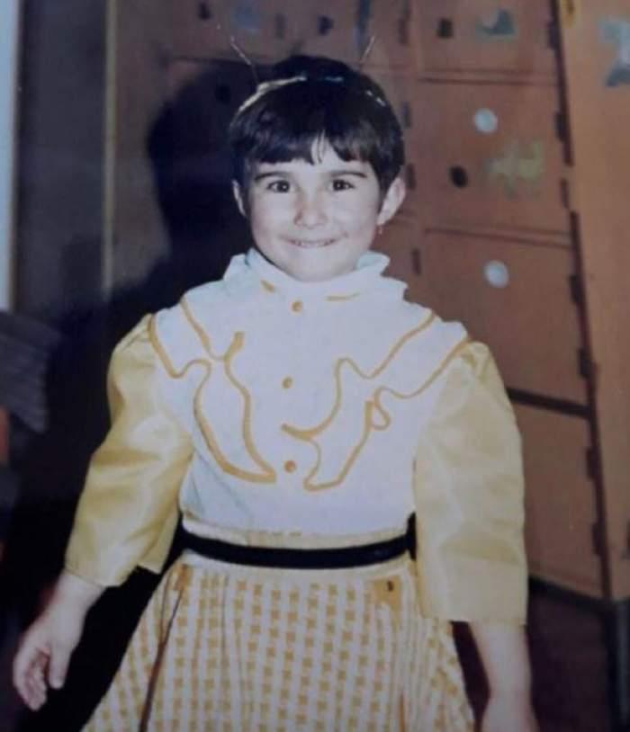 Adda când era copil. Artista avea părul scurt și purta o rochie în nuanțe de alb și galben.