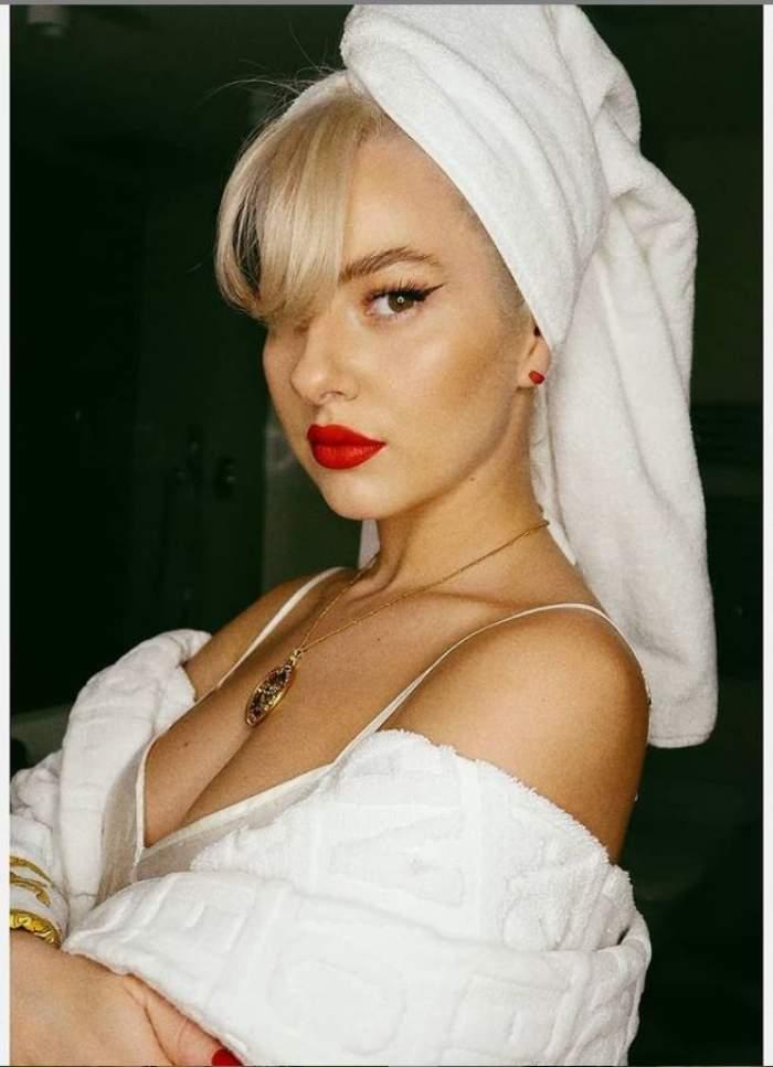 Lidia Buble este intr-un halat de baie alb, poarta un prosop alb pe cap si are ruj rosu