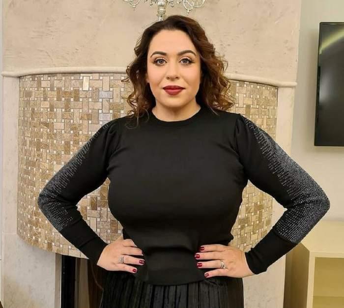Oana Roman poartă o bluză și o fustă neagră. Vedeta își ține mâinile în șold și are părul aranjat în bucle.