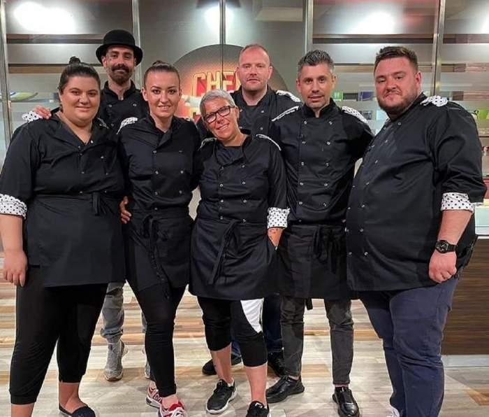 Concurenții chefi la cuțite din sezonul 8. Cu toții poartă uniforme de bucătar negre.