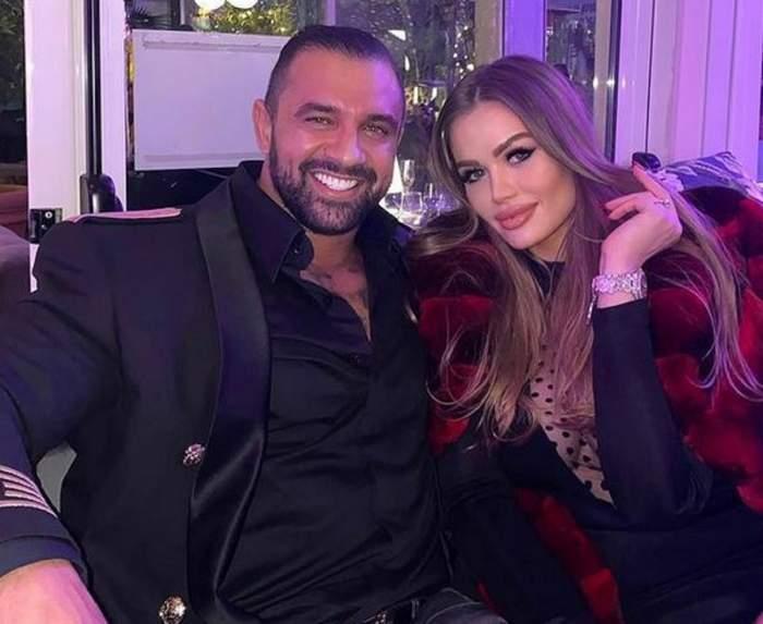 Daria Radionova și Alex Bodi stau pe o canapea, unul lângă altul. Ea poartă o haină de blană roșie, iar el un costum negru.