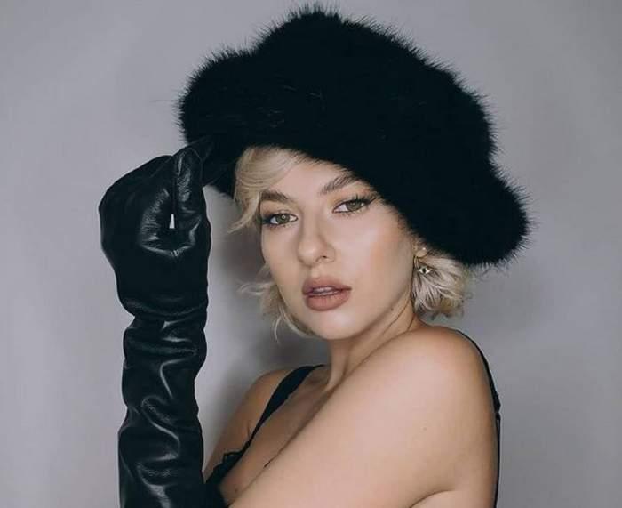 Lidia Buble poartă o pălărie neagră și niște mănuși lungi în aceeași nuanță. Artista e îmbrăcată doar într-un sutien negru.
