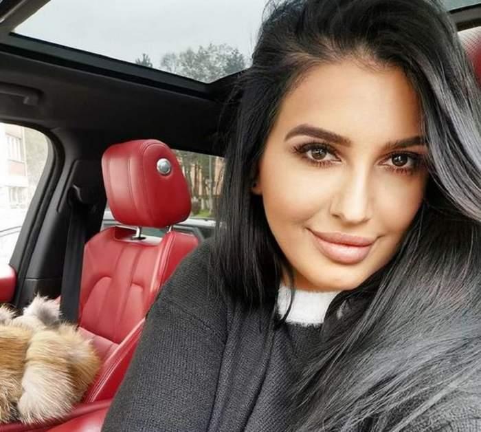 Mirela Banias se află în mașină. Bruneta poartă o bluză neagră și zâmbește. Tapițeria scaunelor este roșie.