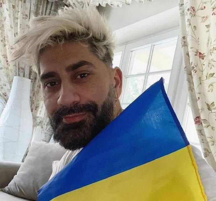 Connect-R poartă un tricou alb. Artistul ține în mână steagul României și zâmbește discret. În spatele lui se poate vedea o veioză albă și niște draperii înflorate.