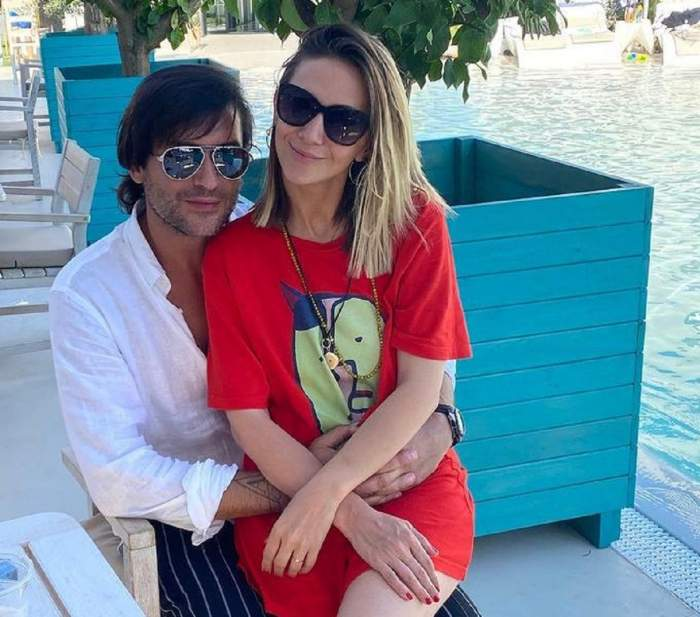 Adela Popescu poartă o rochie roșie, tip tricou, și stă în brațele lui Radu Vâlcan. El poartă o cămașă albă și stă pe scaun.