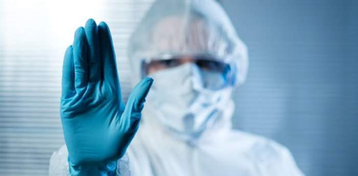Mâna unui medic, cu mănușă, ce arată stoparea pandemiei