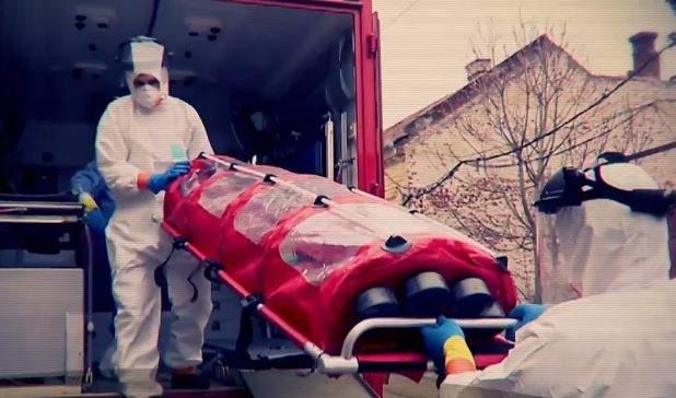 Medici în combinezone, care transportă o persoană infectată