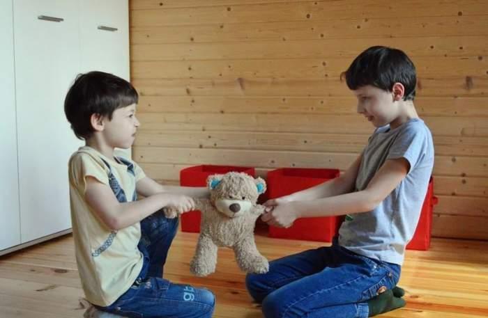 Copii care se ceartă pe o jucărie.