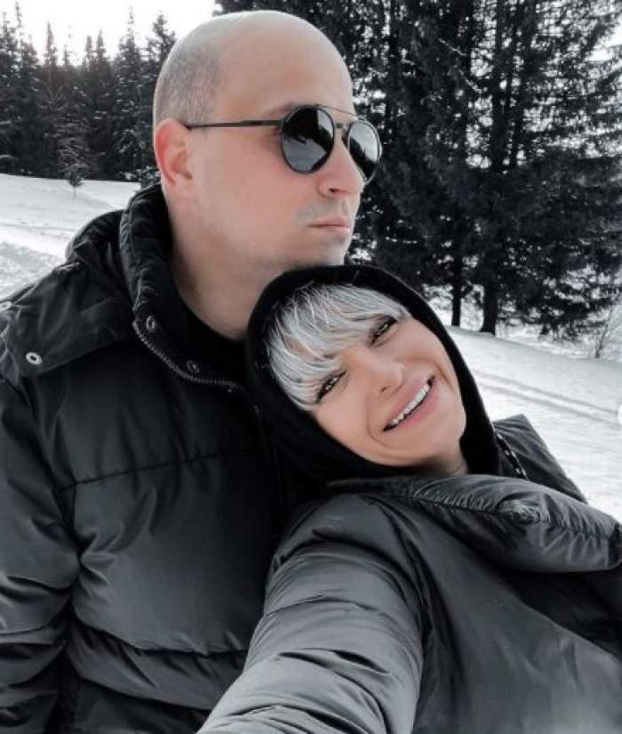 Vlad Huidu și Giulia Anghelescu, îmbrăcați în negru, îmbrățișați la munte