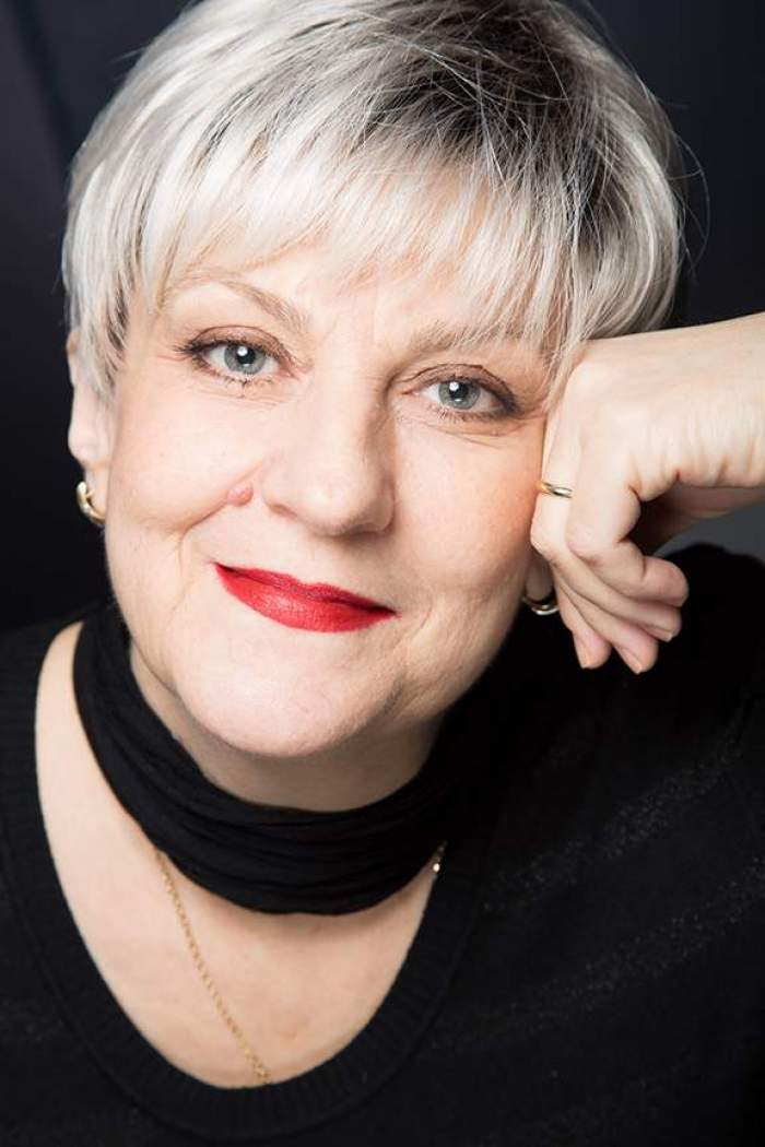 Oana Ștefănescu, îmbrăcată în negru, zâmbtiaore, purtând ruj roșu, cu mâna la față