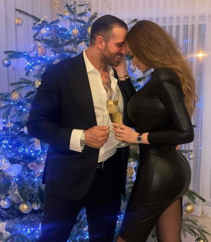 Daria Radionova si Alex Bodi sunt acasa, in fata bradului de Craciun, sunt imbracati eleganti, au o cupa de sampanie in maini, iar el o saruta pe ea pe frunte