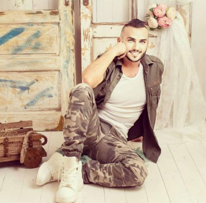Mihai Trăistariu poarta haine kaki, cu un tricou alba, sta in sezut si isi sprijina barbia in pumn, zambeste