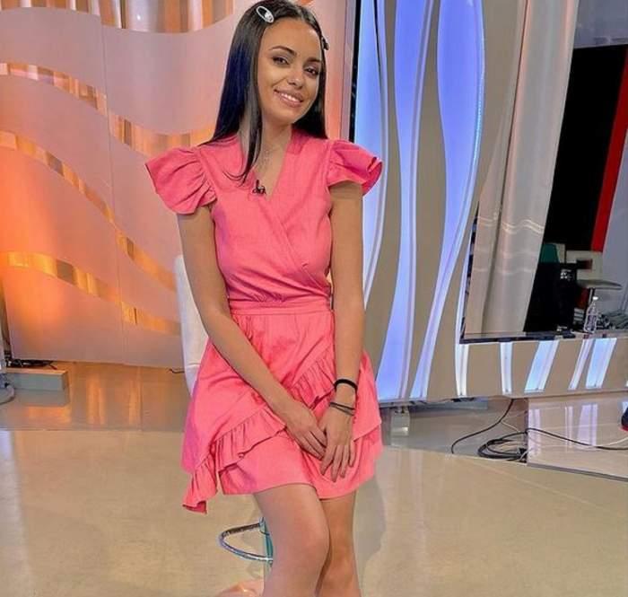 Cosmina Adam se află la Acces Direct. Asistenta tv stă pe un scaun și zâmbește larg. Artista poartă o rochie roz.