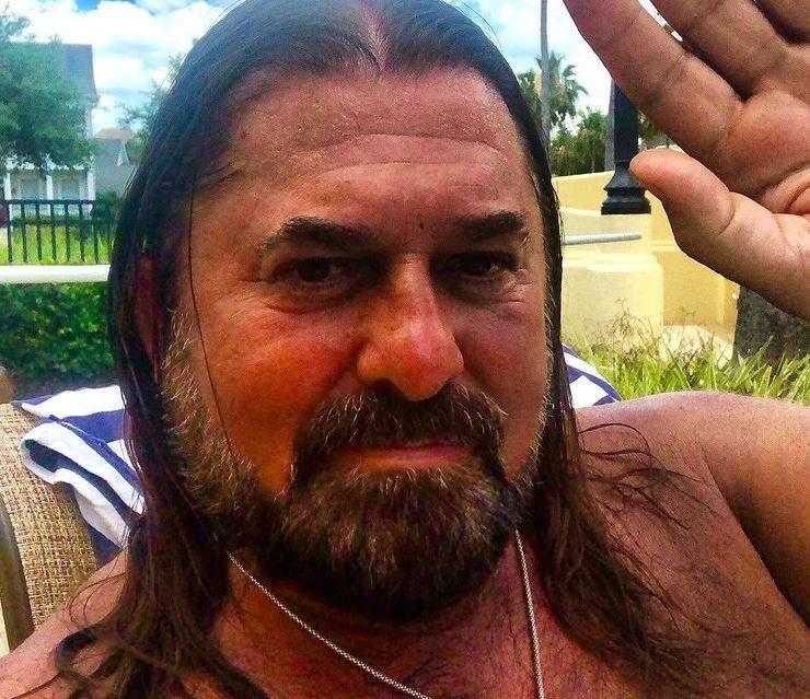 Gheorghe Gheorghiu își face un selfie și ține o mână ridicată, în semn de salut. Artistul nu poartă tricou și are un lanț argintiu la gât.