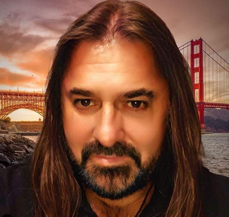 Gheorghe Gheorghiu poartă un tricou negru. În spatele lui se vede un peisaj.