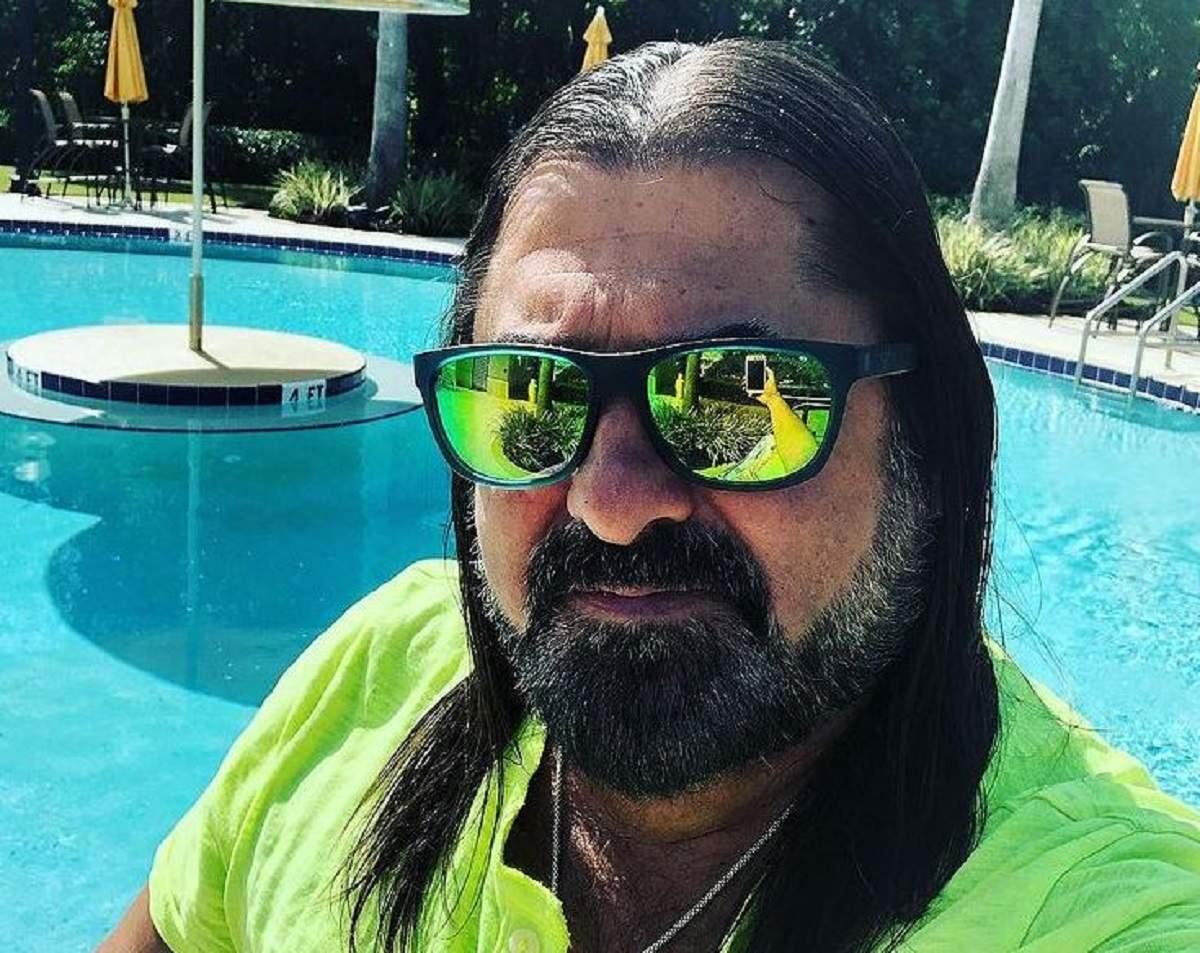 Gheorghe Gheorghiu se află la piscină. Aritstul poartă o pereche de ochelari de soare și un tricou verde.