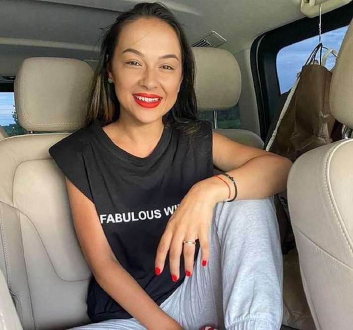 Vlăduța Lupău se află în mașină. Artista poartă un tricou negru cu scris alb și o pereche de pantaloni albi. Vedeta zâmbește larg.