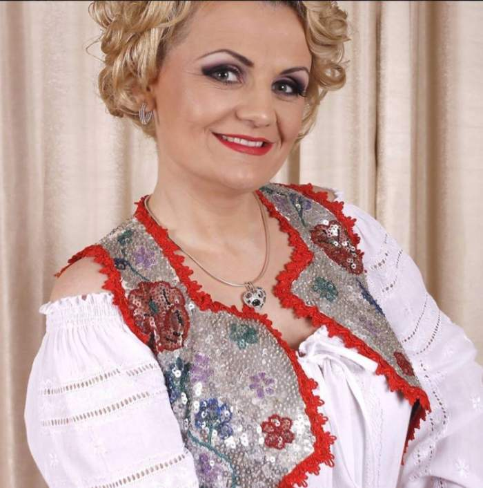 Getei State, în costum tradițional, alb cu roșu, zâmbitoare