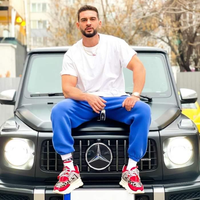 Dorian Popa îmbrăcat în tricou alb și pantaloni albaștri.