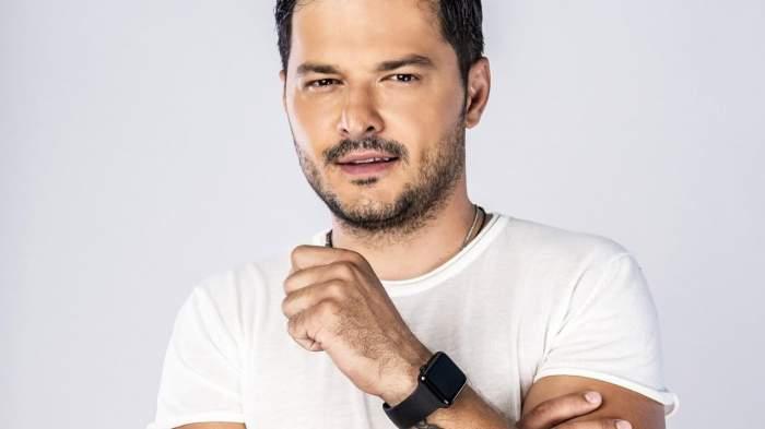 Liviu Vârciu, în tricou alb, cu ceas negru la mână, cu mâna spre barbă
