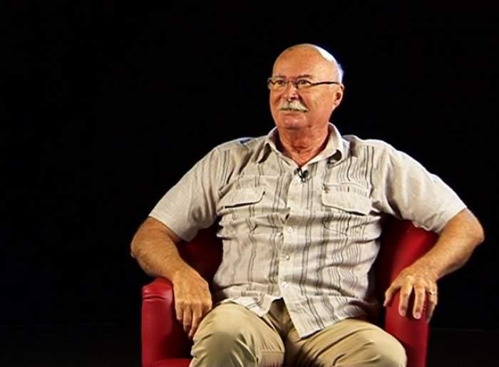 Gheorghe Tudor, în cămașă în carouri, pe scaun roșu, cu un fundal negru în spate