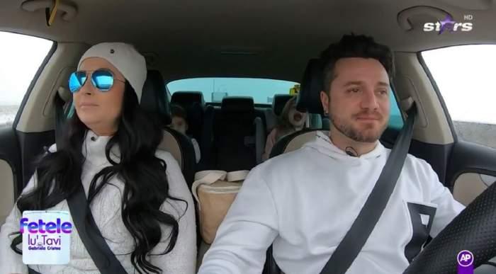 Gabriela Cristea, Tavi Clonda și fetele lor se află în mașină. Prezentatoarea poartă un pulover și o căciulă albă, iar el un hanorac alb.