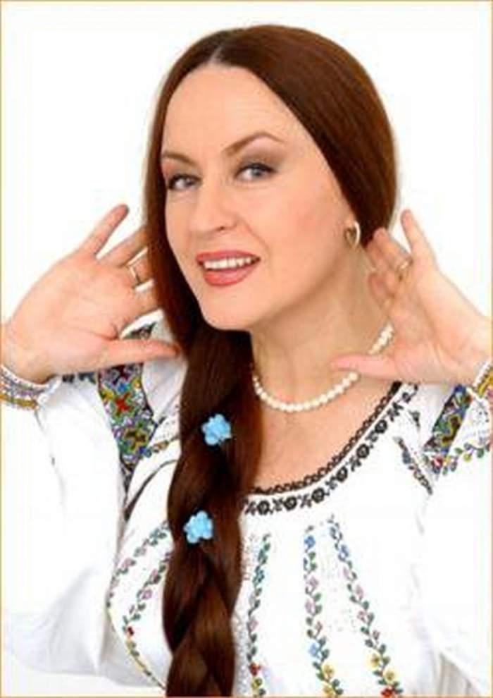 Maria Dragomiroiu, în costum tradițional, alb, cu părul prins în coadă, cu mâinile la gît