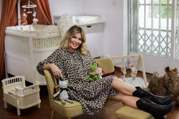 Gina Pistol, în ținută aniamal print, așezată pe fotoliu, lângă pătuțul fetiței