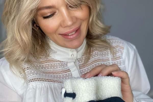 Gina Pistol, în cămașă albă, cu botoșeii fetiței în mână, privindu-i zâmbitoare