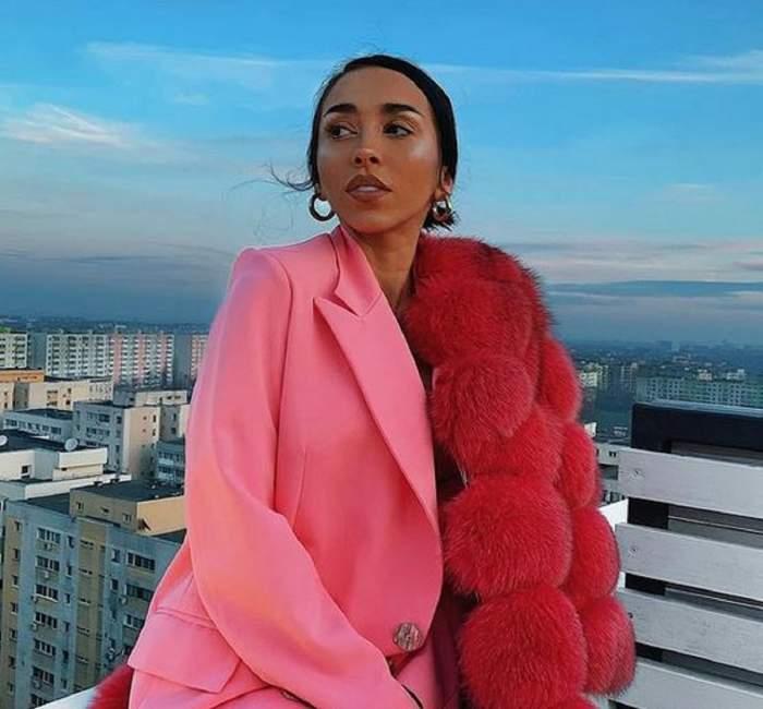 Ruby poartă un costum roz și se află pe balcon. Vedeta are pe umăr o blană roșie și se uită într-o parte.