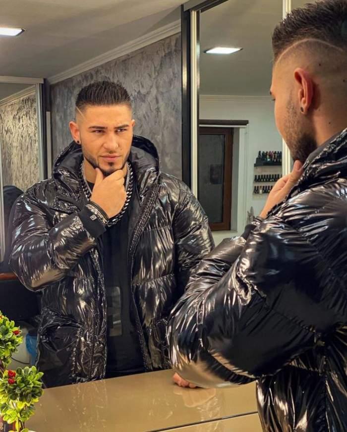 Bogdan Mocanu poarta o geaca de iarna neagra si se uita in oglinda