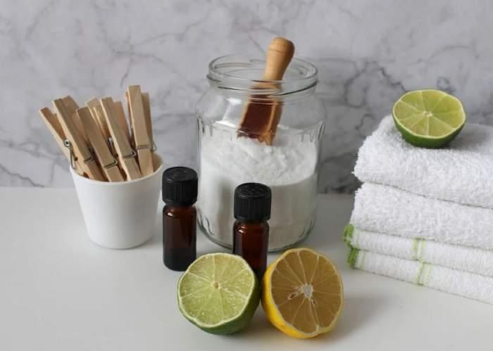 O poză simbol cu bicarbonat de sodiu, lime și lămâie. Lângă aceste ingrediente sunt niște prosoape albe și niște cârlige.