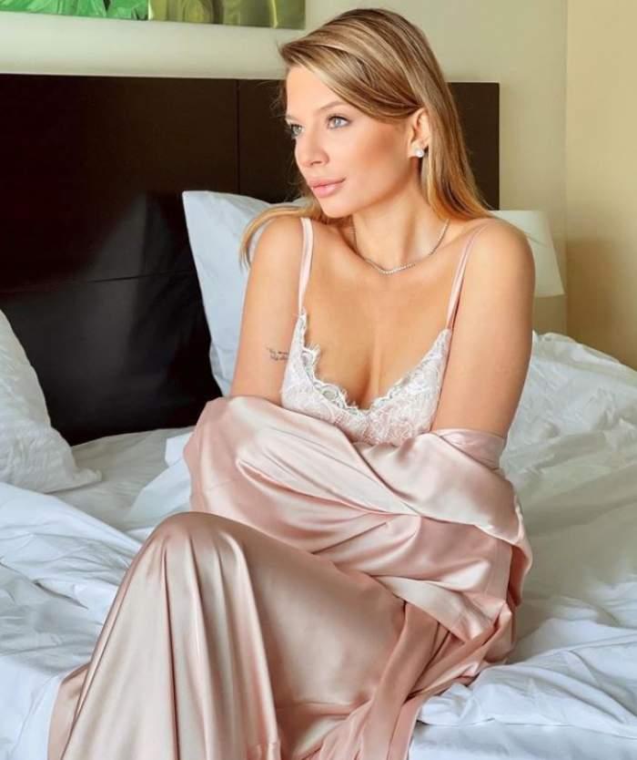 Ana Baniciu poarta o pijama roz din satin, sta pe pat, se uita in fata