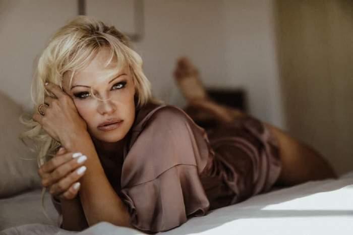 Pamela Anderson stă întinsă pe pat. Artista poartă un combinezon de culoare maro, din satin.